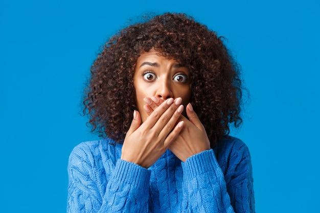 Nahaufnahmeporträt schockiert und erschrocken afroamerikanisches mädchen allein zu hause herz seltsames gruseliges geräusch, keuchend deckmund in panik nicht schreien, knallende augen besorgt, ängstlich stehend.