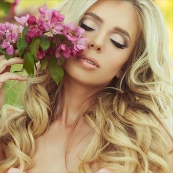 Nahaufnahmeporträt schönen blondine mit rosa blumen