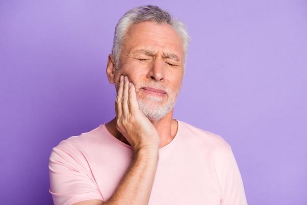 Nahaufnahmeporträt seines hübschen, attraktiven, kranken grauhaarigen mannes, der den wangenkiefer berührt und zahnschmerzen karies fühlt, isoliert über hellem, lebendigem glanz, lebendigem lila lila violetten farbhintergrund