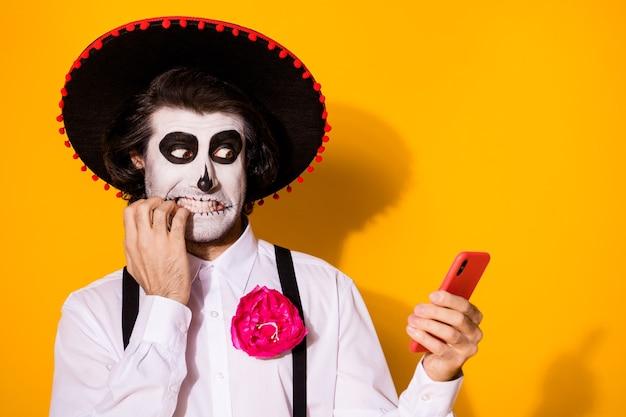 Nahaufnahmeporträt seines nett gemalten gruseligen besorgten nervösen kerls caballero, der ein gadget verwendet, das gefälschte nachrichten blogging, die nägel beißen, einzeln heller, lebendiger glanz, lebendiger gelber farbhintergrund