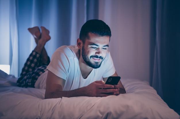 Nahaufnahmeporträt seines netten attraktiven fröhlichen fröhlichen brünetten kerls, der unter verwendung des zellendatumservices auf dem bett liegt und sms-freies wochenende wochenende am späten abend nach hause hotelzimmerwohnung drinnen sendet