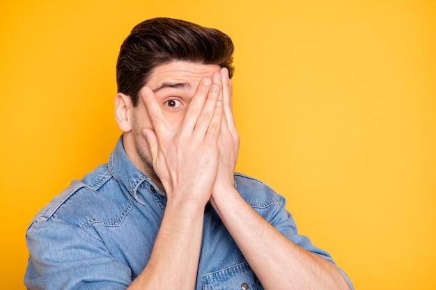 Nahaufnahmeporträt seines netten attraktiven gutaussehenden funky lustigen kindischen kerls, der gesicht hinter palmen versteckt, das vermeidet, isoliert über hell lebendigen glanz leuchtend gelbe farbwand spähen