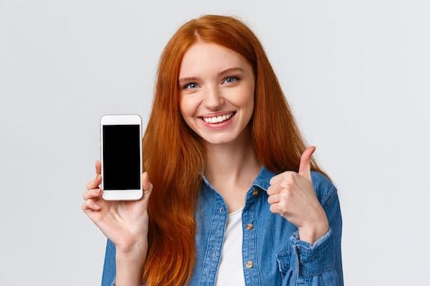 Nahaufnahmeporträt stellte die schöne rothaarigefrau zufrieden, die anwendung verwendet, empfehle, sie herunterzuladen, foto-app annoncierend, onlineshop, show-smartphoneanzeige und daumen-oben, wie