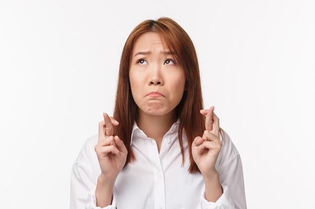 Nahaufnahmeporträt traurig elend süßes asiatisches mädchen schluchzt und schaut verärgert auf, wünscht sich, schaut verärgert, drückt die daumen viel glück, fleht, will etwas wahr werden, erwartet gutes ergebnis hoffnungslos