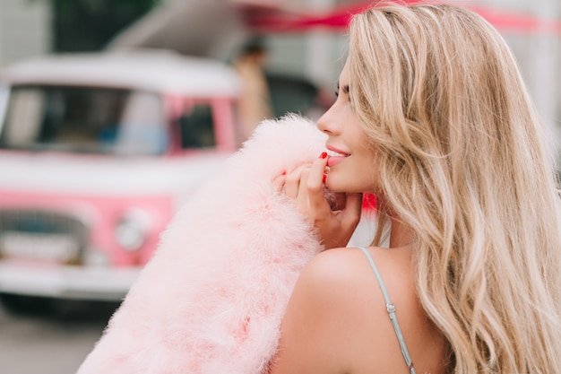 Nahaufnahmeporträt vom hinteren stift oben gestyltes mädchen, das rosa pelzstola auf retro-autohintergrund hält. sie hält den finger auf den lippen und lächelt zur seite.