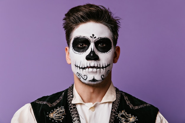 Nahaufnahmeporträt von brunet mit gesicht gemalt für halloween. braunäugiger mann im weißen hemd