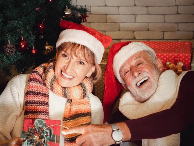 Nahaufnahmeporträt von glücklichen älteren kaukasischen paaren mit dem weihnachtsmann-hut, der weihnachtsgeschenk hält, feiern zusammen zu hause. warmer und romantischer winterurlaub.