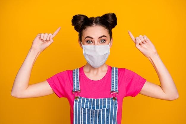 Nahaufnahmeporträt von ihr, einem hübschen, hübschen, braunhaarigen mädchen, das eine sicherheitsmaske trägt, die eine neue frisur zeigt, um die prävention von atemwegserkrankungen zu stoppen, isolierter leuchtend gelber farbhintergrund