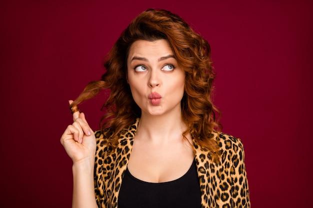 Nahaufnahmeporträt von ihr hübsch aussehende, hübsche hübsche, neugierige, flirty, gewellte, schmollende dame, die mit locken spielt, einzeln auf dunklem kastanienbraunem burgunder-marsala-farbhintergrund