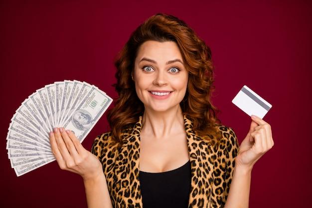 Nahaufnahmeporträt von ihr hübsch aussehendes attraktives hübsches hübsches reiches fröhliches fröhliches, gewelltes mädchen, das in der hand budgetkarte hält, einzeln auf rotem kastanienbraunem burgunder-marsala-farbhintergrund