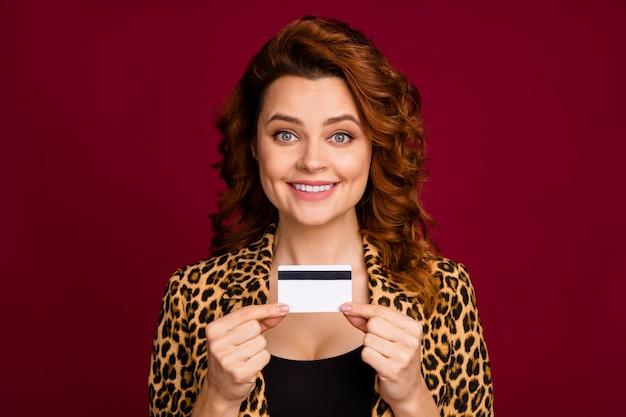 Nahaufnahmeporträt von ihr hübsch aussehendes, hübsches, charmantes, fröhliches, fröhliches, gewelltes mädchen, das in den händen eine neue kreditkarte hält, einzeln auf rotem kastanienbraunem burgunder-marsala-farbhintergrund