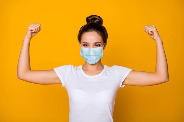 Nahaufnahmeporträt von ihr hübsches attraktives hübsches mädchen mit sicherheitsgazemaske, die bizepsmuskeln demonstriert, stoppt virale lungenentzündung mers cov influenza isoliert leuchtend gelber farbhintergrund