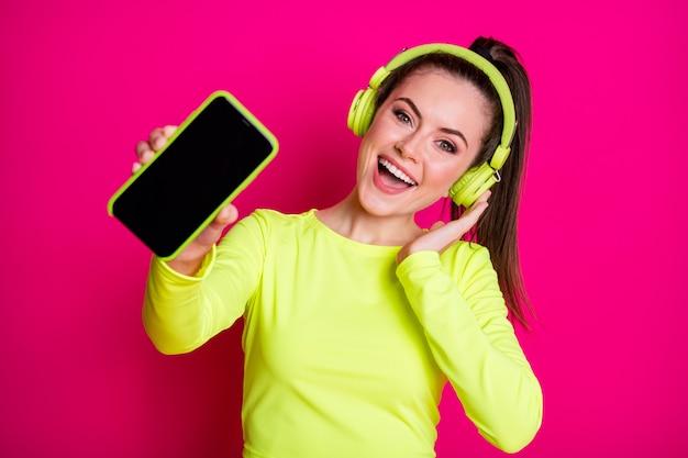 Nahaufnahmeporträt von ihr, sie attraktives hübsches, charmantes, fröhliches, fröhliches mädchen, das popmusik hört, die bildschirm-gadget zeigt, isoliert heller, lebendiger glanz, lebendiger pinkfarbener, fuchsiafarbener hintergrund