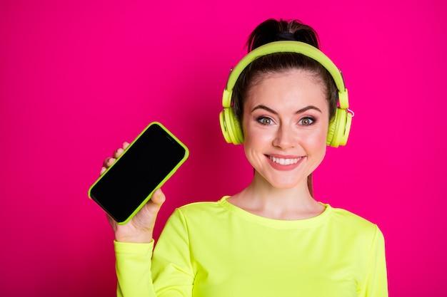 Nahaufnahmeporträt von ihr, sie attraktives hübsches hübsches, charmantes, fröhliches, fröhliches mädchen, das popmusik hört, die das bildschirmgerät zeigt, isoliert heller, lebendiger glanz, vibrierender rosafarbener, fuchsiafarbener hintergrund