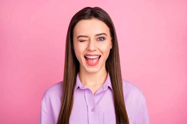 Nahaufnahmeporträt von ihr, sie ist ein hübsches, attraktives, hübsches, fröhliches, liebenswertes langhaariges mädchen, das spaß hat, ihnen einzeln über rosafarbenem pastellfarbenhintergrund zu zwinkern