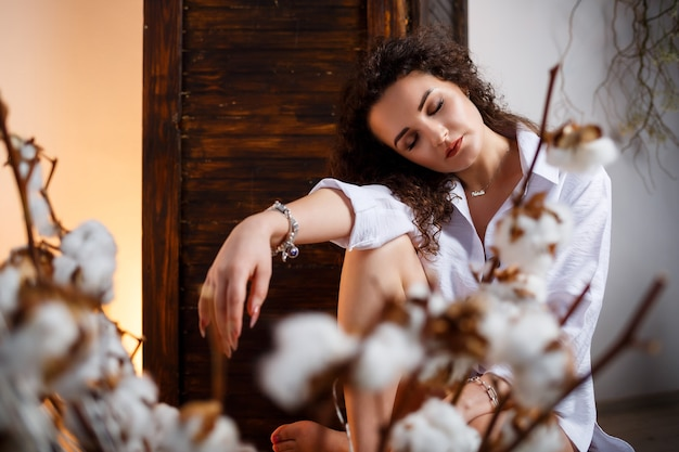 Nahaufnahmeporträt von ihr, sie ist schön, attraktiv, lieblich, fröhlich, mit welligem haar, mädchen, das spaß hat, lächelt, auf hellem, pastellfarbenem hintergrund, weiße blumen, weißes hemd