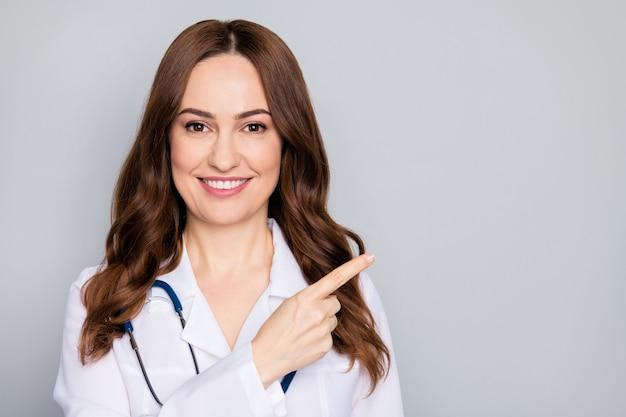 Nahaufnahmeporträt von ihr sie schönes attraktives fröhliches wellenförmiges doc-phonendoskop-stethoskop zeigt kopierraumentscheidung isoliert über grauem pastellfarbenhintergrund
