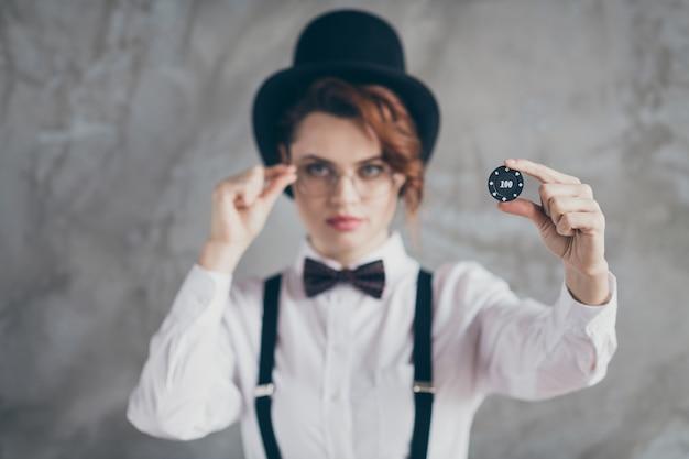 Nahaufnahmeporträt von ihr, sie verwischte schöne attraktive, ernsthafte, gewellte mädchenfrau, die in der hand hält, und gibt ihnen münzzeichen, um glücksvermögen einzeln auf grauem betonindustriewandhintergrund zu versuchen