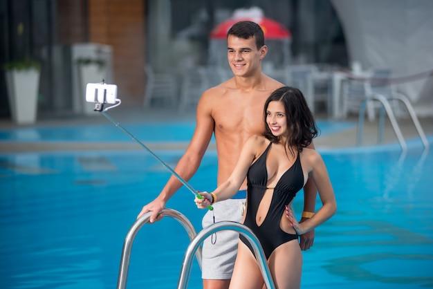 Nahaufnahmeporträt von jungen paaren mit der perfekten zahl, die gegen den swimmingpool aufwirft