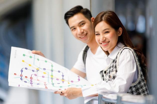 Nahaufnahmeporträt von netten lächelnden jungen asiatischen paartouristen, die papierkarte auf überführungssteg suchen und halten. selektiver fokus auf eine frau mit verschwommenem mann und hintergrund