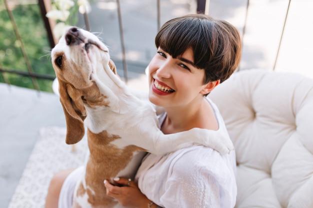 Nahaufnahmeporträt von oben des lachenden mädchens, das morgen auf balkon mit lustigem haustier genießt. schöne junge dame in guter laune, die mit beagle-hund spielt, während sie sich nach dem abendessen auf der terrasse ausruht
