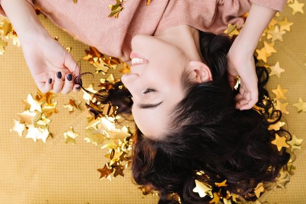 Nahaufnahmeporträt von oben junge freudige frau mit geschnittenem lockigem haar, das spaß in goldenen lametta auf couch zu hause hat. schöne gemütlichkeit eines hübschen modells, das positivität ausdrückt