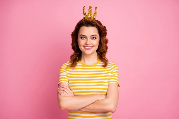 Nahaufnahmeporträt von reichen, wohlhabenden verschränkten armen tragen eine krone, die über rosafarbenem hintergrund isoliert ist