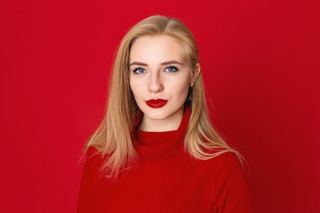 Nahaufnahmeporträt von sinnlichen blondinen gegen einen roten hintergrund im studio.