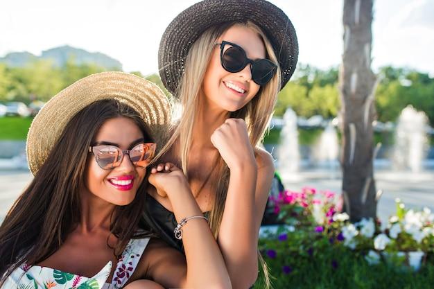 Nahaufnahmeporträt von zwei attraktiven blonden und brünetten mädchen mit langen haaren, die zur kamera im park aufwerfen. sie lächeln zur seite.