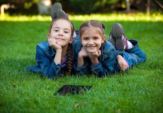 Nahaufnahmeporträt von zwei kleinen mädchen, die mit tablet auf gras liegen