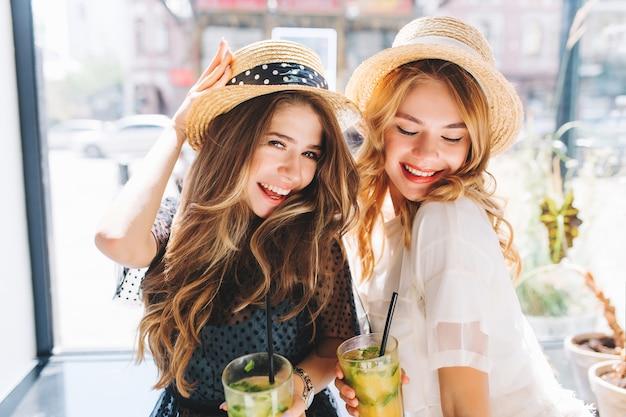 Nahaufnahmeporträt von zwei mädchen in eleganter kleidung, die spaß zusammen in den sommerferien haben