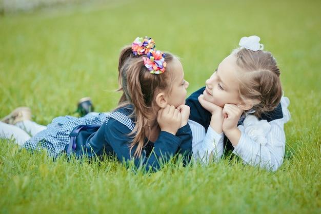 Nahaufnahmeporträt von zwei netten attraktiven gewinnenden reizenden reizenden niedlichen freundlichen fröhlichen schwestern, die in der frischen luft des grünen grases liegen, die urlaubsferienwochenende verbringen, die einander betrachten
