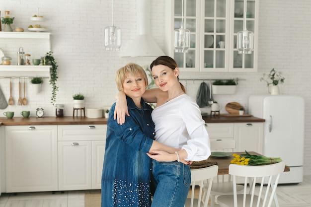 Nahaufnahmeporträt von zwei schönen attraktiven schönen zarten fröhlichen frauen mutter mama erwachsene tochter verbringen zeit tag zusammen in weißlicht innenhaus wohnung wohnung drinnen