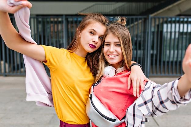 Nahaufnahmeporträt von zwei verträumten mädchen in der sommerkleidung, die mit vergnügen vor modeboutique aufwirft