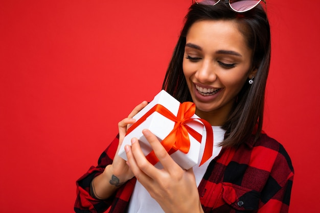 Nahaufnahmeporträtfoto der schönen glücklichen jungen weiblichen brunetperson lokalisiert auf roter hintergrundwand