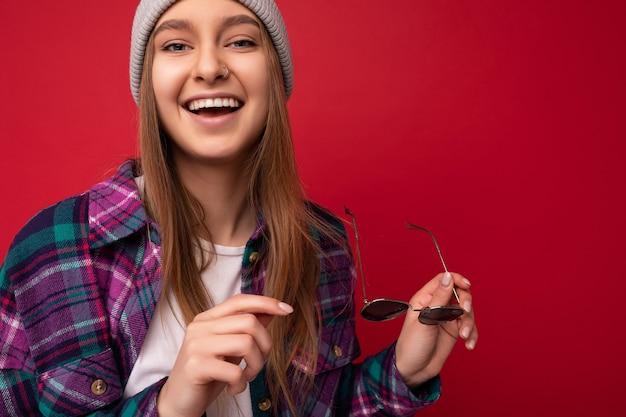 Nahaufnahmeporträtfoto der schönen glücklichen lächelnden jungen dunkelblonden frau lokalisiert über rotem hintergrund, die buntes stilvolles hemd und moderne sonnenbrille trägt, die kamera betrachtet.