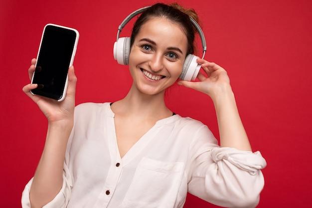 Nahaufnahmeporträtfoto der schönen glücklichen lächelnden jungen frau, die stilvolles lässiges outfit isoliert trägt wearing