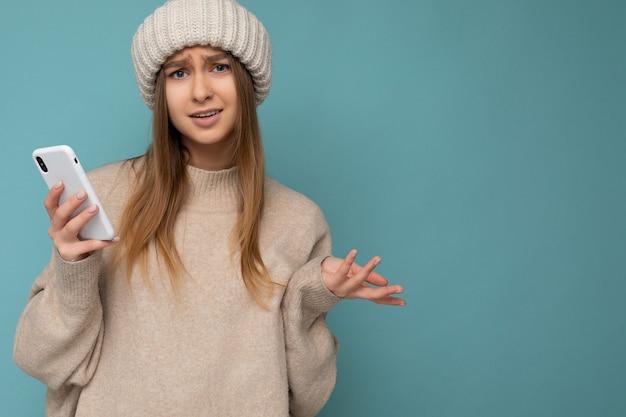 Nahaufnahmeporträtfoto der schönen unzufriedenen jungen blonden frau, die stylisches beige warm trägt