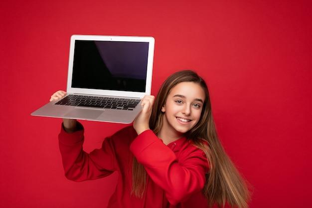 Nahaufnahmeporträtfoto des schönen glücklichen lächelnden mädchens mit dem langen haar, das roten hoodie trägt, der computerlaptop hält, der kamera lokalisiert über rotem wandhintergrund betrachtet. attrappe, lehrmodell, simulation