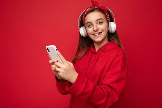 Nahaufnahmeporträtfoto des schönen positiven lächelnden weiblichen teenagers, der roten hoodie trägt