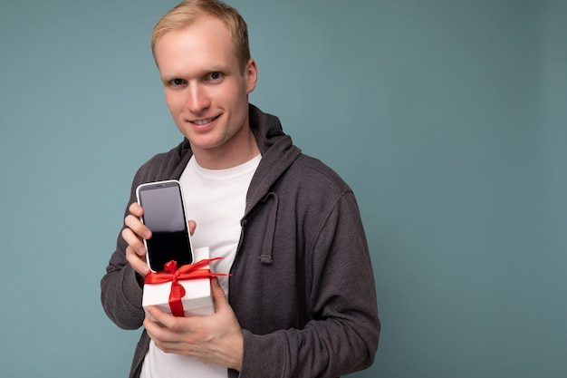 Nahaufnahmeporträtfoto eines coolen, gutaussehenden, glücklichen jungen mannes mit grauem pullover und weißem t-shirt, der isoliert über blauer hintergrundwand steht und smartphone hält und telefon mit leerem bildschirm zeigt