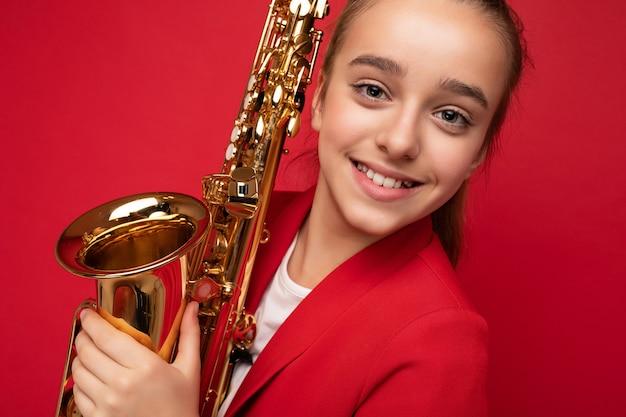 Nahaufnahmeporträtfotoaufnahme eines schönen, glücklich lächelnden, brünetten kleinen mädchens, das eine stilvolle rote jacke trägt, die isoliert über der roten hintergrundwand steht, die saxophon an der kamera hält.