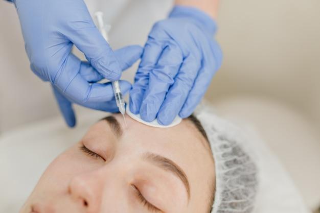 Nahaufnahmeporträthände in blauen klinikhandschuhen, die injektion auf frauengesicht machen. verjüngung, injektion, professionelle therapie, gesundheitswesen, plastik, botox, schönheit