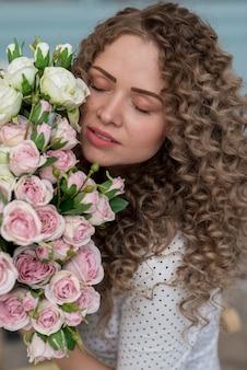 Nahaufnahmeportrair des hübschen mädchens mit blumenstrauß von rosen und von geschlossenen augen. - bild