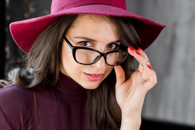 Nahaufnahmeportrait der jungen schönen modernen frau mit brillen und hut über ihrem kopf