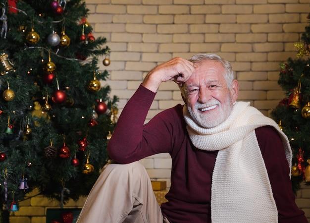 Nahaufnahmeportrait des lächelnden hübschen kaukasischen älteren mannes im roten pullover und im schal, der vor geschmücktem weihnachtsbaum sitzt. winterurlaub entspannen.