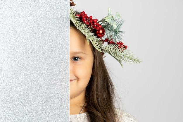 Nahaufnahmeportrait des lächelnden wunderbaren mädchens im weihnachtsbaumkranz, das halbes gesicht hinter silbernem s...