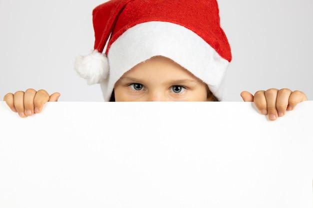 Nahaufnahmeportrait des mädchens in der roten weihnachtsmütze, das weißes leeres plakat isoliert auf weißem hintergrund m...