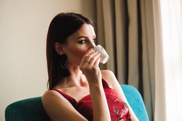 Nahaufnahmeportrait des trinkenden kaffees der schönen frau