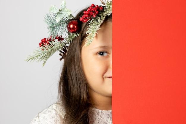 Nahaufnahmeportrait eines sechsjährigen kaukasischen mädchens im weihnachtskranz versteckt halbes gesicht hinter roten leeren ...